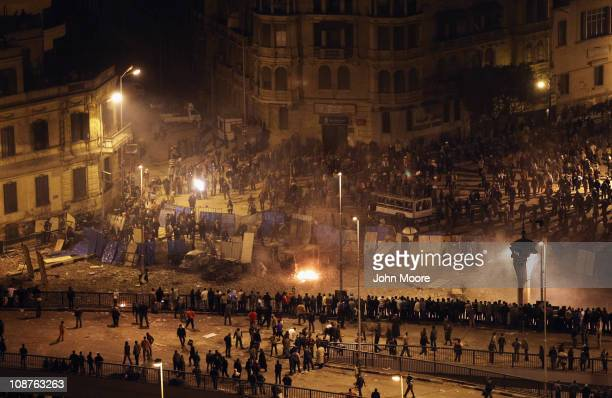 Antigovernment demonstrators hide behind makeshift shields as Molotof cocktails are lobbed by supporters of Egyptian President Honsi Mubarak early on...