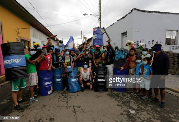 Antigovernment demonstrators holding makeshift shields and mortars pose in front of a barricade during protests in the town of Masaya 35 km from...