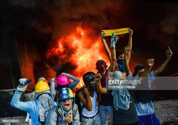 TOPSHOT Antigovernment demonstrators participate in an attack to the administration headquarters of the Supreme Court of Justice as part of protests...