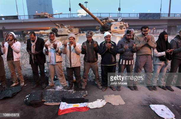 Antigovernment demonstrators pray at sunset in front of Egyptian army tanks on February 5 2011 in Cairo Egypt The army had planned to clear the...