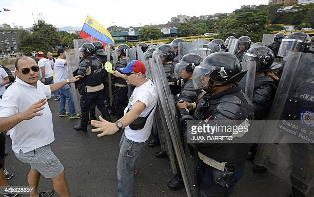 Antigovernment demonstrators struggle with members of the National Guard during a protest in eastern Caracas on February 27 2014 Dueling demos of pro...