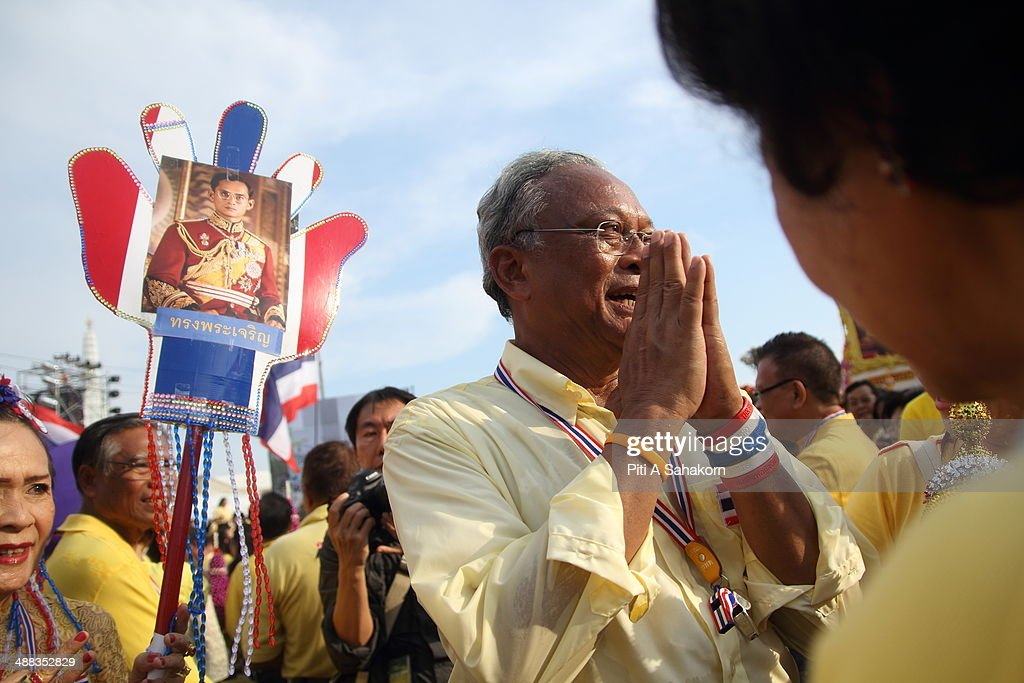 Anti-government leader Suthep Thaugsuban greets his supporters during a rally showing their loyalty to King Bhumibol Adulyadej on the 64th anniversary of his Coronation Day. Thailand's revered King Bhumibol Adulyadej made a rare public appearance to mark the 64th anniversary of his coronation. Thailand's Election Commission and the caretaker government agreed to hold new elections on 20 July 2014 after several months of political turmoil and uncertainty while anti-government protesters calling the resignation of caretaker Prime Minister Yingluck Shinawatra and demanding political reforms before any new elections.