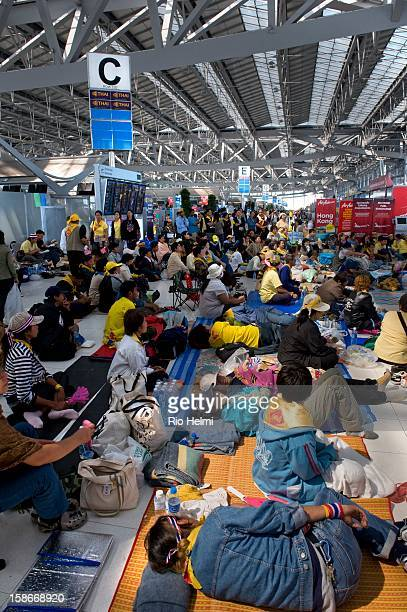 Antigovernment People's Alliance for Democracy supporters occupying the international terminal at Suvarnabhumi airport crowd around a television set...