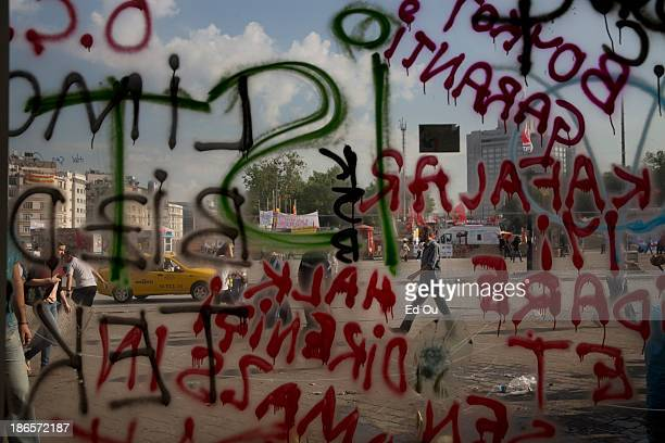 Anti-government protest graffiti sprayed over the weekend during mass protests is seen through the windows of a bank in Taksim Square in Istanbul,...