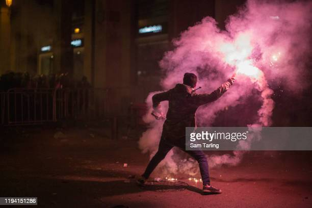 Anti-government protester throws a flare at riot police as they clashed for the second day in a row near the Parliament building on Sunday 15...