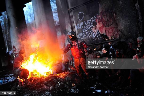 Antigovernment protester warm themselves at a fire at the barricade on Hrushevskoho Street Kiev on January 29 2014 in Kiev Ukraine Ukraine's Prime...