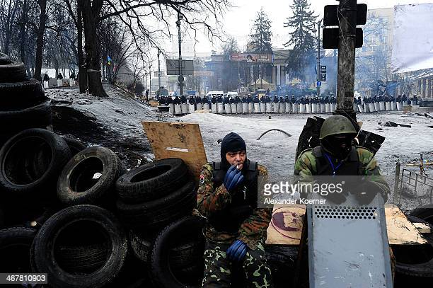 Antigovernment protesters are pictured while smoking in front of a barricade on Hrushevskoho Street on February 8 2014 in Kiev Ukraine Opponents of...