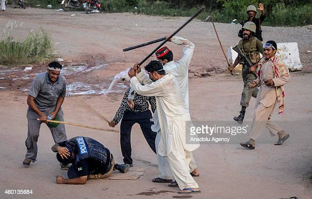Antigovernment protesters armed with batons beat a policeman during clashes in Islamabad Pakistan on September 1 2014 Clashes erupted between the...