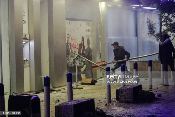 Anti-government protesters attack a bank in the Lebanese coastal city of Tripoli north of Beirut on January 21 as they protest the newly-announced...