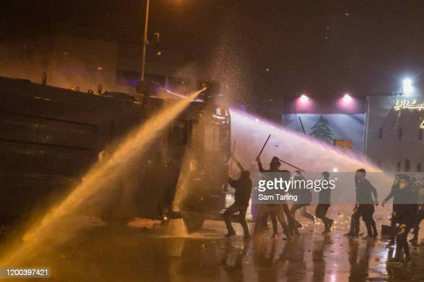 Anti-government protesters attack a water cannon truck as they clash with riot police, on January 18 in Beirut, Lebanon. According to the Red Cross,...