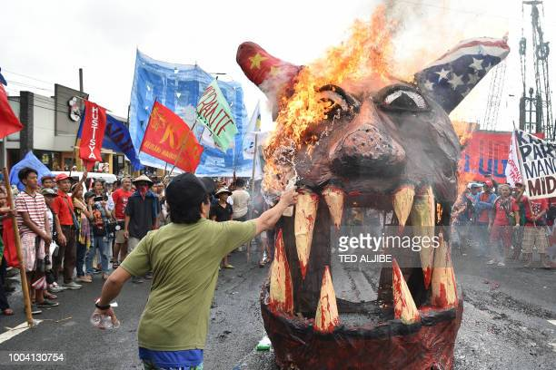Antigovernment protesters burn an effigy depicting Philippine's President Rodrigo Duterte with horns decorated with the national flags of China and...