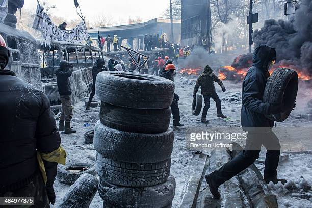Antigovernment protesters burn tires during clashes with police on Hrushevskoho Street near Dynamo stadium on January 25 2014 in Kiev Ukraine After...