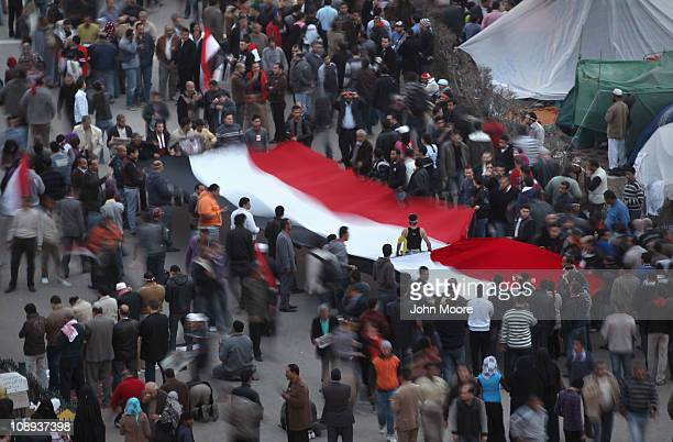 Antigovernment protesters carry a banner of the Egyptian flag through Tahrir Square on February 9 2011 in Cairo Egypt More than two weeks into...