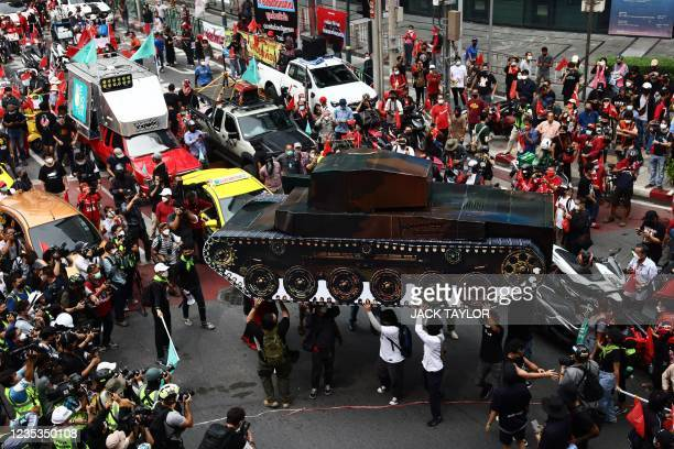 Anti-government protesters carry a large replica of a tank as they gather for a demonstration to mark the 15-year anniversary of the 2006 military...