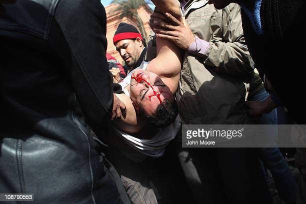 Antigovernment protesters carry a suspected plain clothes policeman for treatment after he was hit by a rock on February 3 2011 in Cairo Egypt He and...