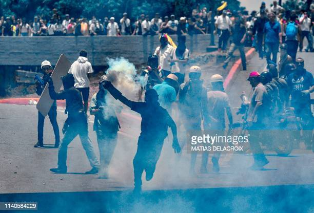 Antigovernment protesters clash with security forces in the surroundings of La Carlota military base in Caracas during the commemoration of May Day...