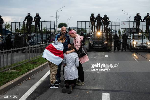 Anti-government protesters console a praying woman near riot police on August 23, 2020 in Minsk, Belarus. There have been near daily demonstrations...