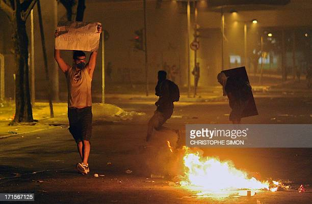 Antigovernment protesters demonstrate during clashes with the police outside the Mineirao stadium in Belo Horizonte on June 26 2013 where Brazil and...