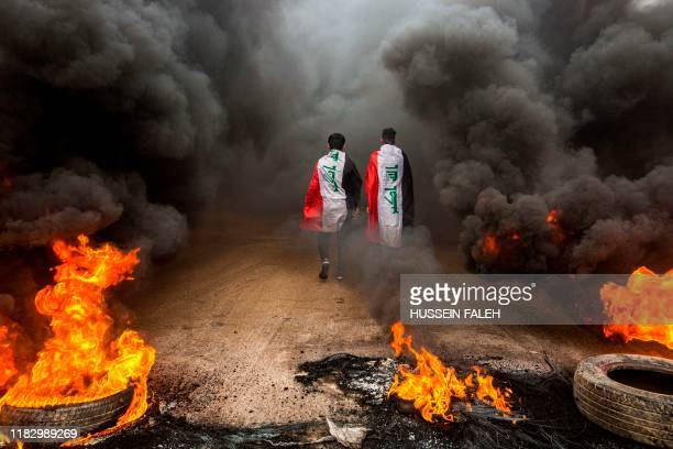 Anti-government protesters draped in Iraqi national flags walk into clouds of smoke from burning tires during a demonstration in the southern city of...