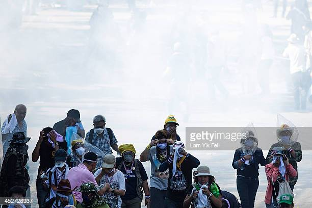 Antigovernment protesters escape after riot police fire tear gas on December 1 2013 in Bangkok Thailand Antigovernment protesters in Bangkok say they...