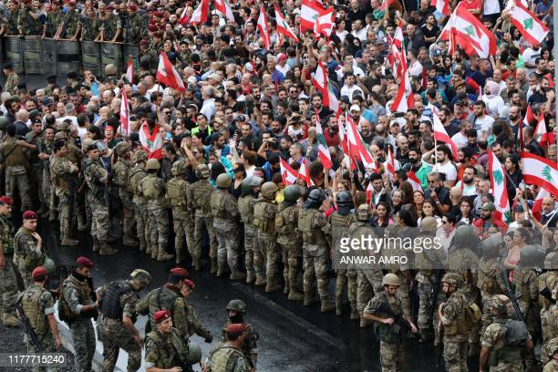 TOPSHOT Antigovernment protesters facing Lebanese army soldiers wave national flags in the area of Jal alDib in the northern outskirts of the...