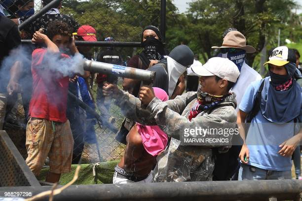 Antigovernment protesters fire a homemade mortar during clashes within the 'Marcha de las Flores' in Managua on June 30 2018 At least six people were...