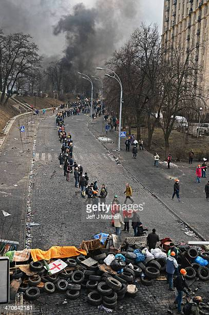Antigovernment protesters form a human chain as they carry rocks and tyres to rebuild barricades following continued clashes with police in...