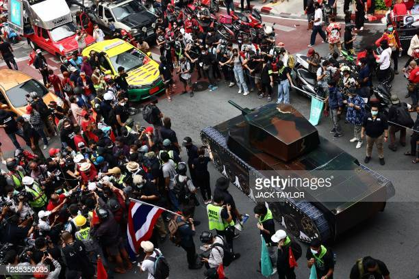 Anti-government protesters gather around a large replica of a tank as they gather for a demonstration to mark the 15-year anniversary of the 2006...
