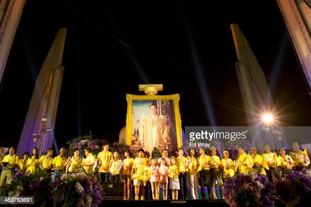 AntiGovernment protesters gather before a large portrait of the Thai King Bhumibol Adulyadej' during a mass celebration of his 86th birthday at the...