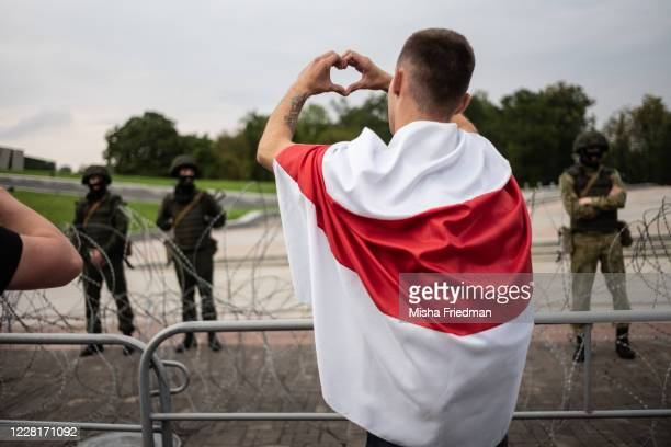 Anti-government protesters gesture as they walk past riot police on August 23, 2020 in Minsk, Belarus. There have been near daily demonstrations...