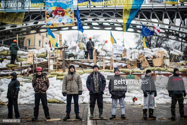 Antigovernment protesters guard a barricade designed to keep police from evicting them from Independence Square on December 13 2013 in Kiev Ukraine...