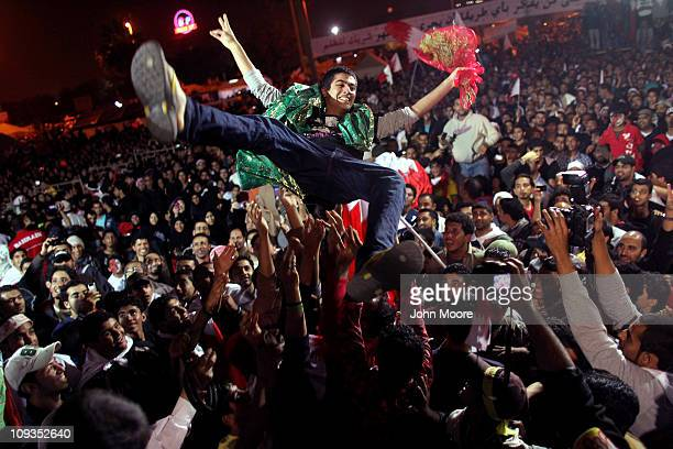 Anti-government protesters hoist a released political prisoner in the air in the Pearl roundabout late on February 22, 2011 in Manama, Bahrain....