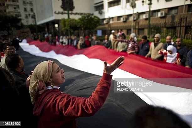 Antigovernment protesters hold a giant Egyptian flag as they shout slogans against President Hosni Mubarak outside the parliament located some 500m...