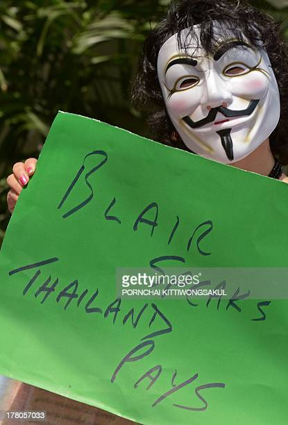 Antigovernment protesters hold a placard as they protest former British prime minister Tony Blair to give a speech at an upcoming governmentsponsored...