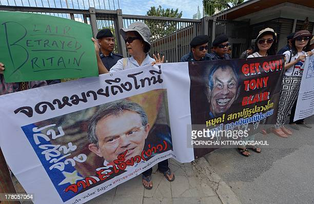 Antigovernment protesters hold placards as they protest former British prime minister Tony Blair to give a speech at an upcoming governmentsponsored...