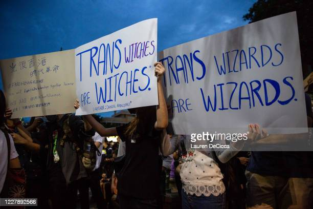 Antigovernment protesters hold signs calling out JK Rowling's transphobic twitter comments as they take part in a Harry Potter themed rally in front...