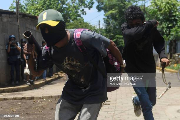 Antigovernment protesters hold their homemade mortars and sling shots during clashes with riot police and members of the Sandinista youth in Masaya...