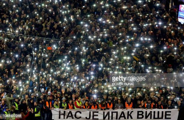 TOPSHOT Antigovernment protesters hold up their phones and candles and hold a banner in Cyrillic writing that reads 'Still there is more of us' as...