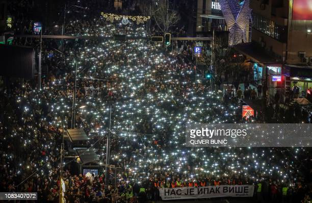 Antigovernment protesters hold up their phones and candles and hold a banner in Cyrillic writing that reads 'Still there is more of us' as they...