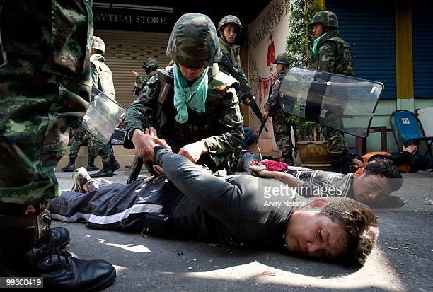 Antigovernment protesters lie on the ground while being detained by Thai military forces during street clashes on May 14 2010 in Bangkok Thailand...