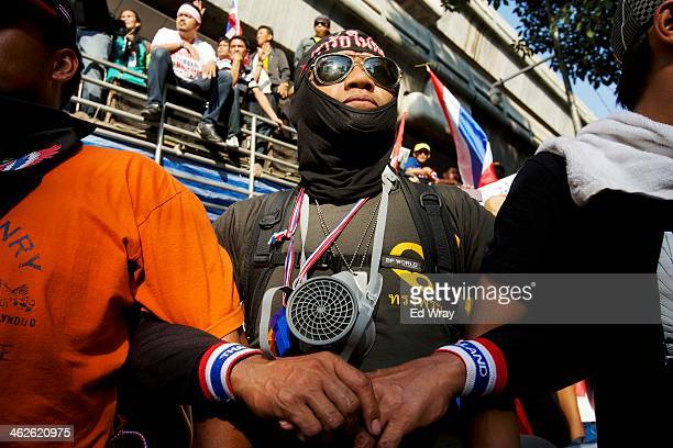 Antigovernment protesters link arms as they protest in front of the Royal Thai Police headquarters on January 14 20134 in Bangkok Thailand More...