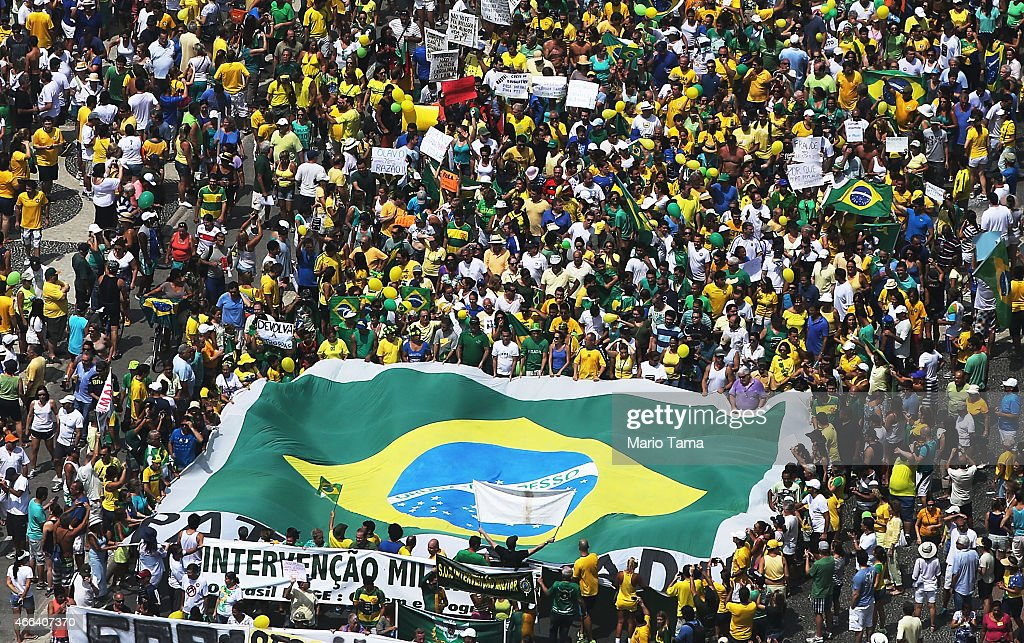 Anti-government protesters march carrying a Brazilian flag along Copacabana beach on March 15, 2015 in Rio de Janeiro, Brazil. Protests across the country were held today against President Dilma Rousseff's government with many protesters calling for her impeachment. A massive corruption scandal at Brazil's state-owned oil company Petrobras has rocked the government and Dilma's approval ratings are now around 23 percent. Brazil's inflation rate has hovered around ten-year highs recently while the currency, the Brazilian real, has passed twelve-year lows when measured against the U.S. dollar.