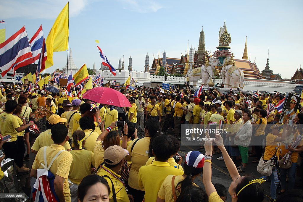 Anti-government protesters march during a rally showing their loyalty to King Bhumibol Adulyadej on the 64th anniversary of his Coronation Day. Thailand's revered King Bhumibol Adulyadej made a rare public appearance to mark the 64th anniversary of his coronation. Thailand's Election Commission and the caretaker government agreed to hold new elections on 20 July 2014 after several months of political turmoil and uncertainty while anti-government protesters calling the resignation of caretaker Prime Minister Yingluck Shinawatra and demanding political reforms before any new elections.