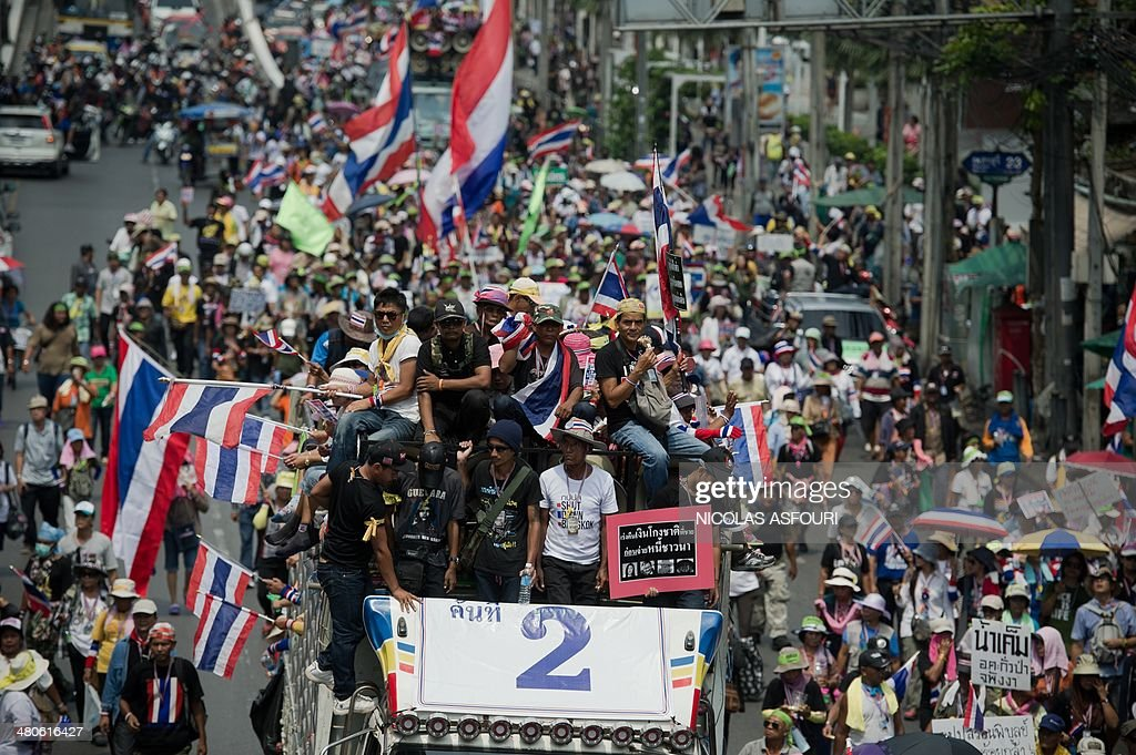 Anti-government protesters march in a street during a rally in Bangkok on March 26, 2014. Anti-government protesters have resumed daily marches through Bangkok to build up support after a general election held last month was declared invalid in a ruling from the Constitutional Court on March 21 following disruption by opposition protesters. AFP PHOTO/ Nicolas ASFOURI