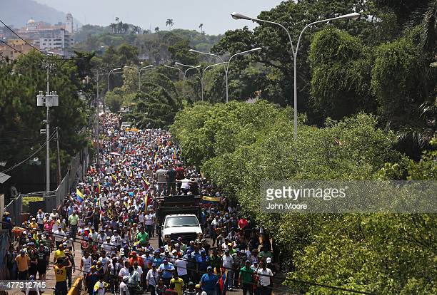 Antigovernment protesters march on March 8 2014 in San Cristobal the capital of Tachira state Venezuela Shortage of such products as flour milk and...