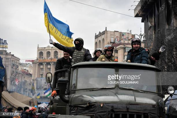 Antigovernment protesters one holding the Ukrainian national flag drive a military vehicle at the Independence square in central Kiev on February 22...