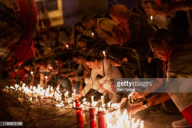 Anti-government protesters place candles by razor wire outside the government headquarters in Riadh Al Solh square, on November 6, 2019 in Martyrs'...