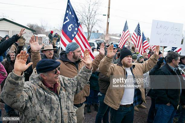 Antigovernment protesters raise their arms in the air and shout 'hands up don't shoot' outside the Harney County Courthouse on February 1 2016 in...