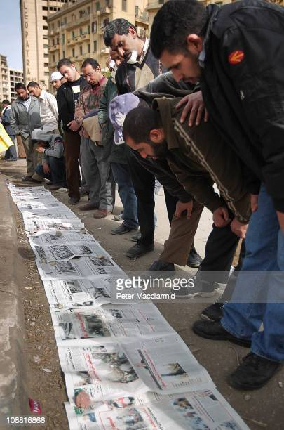 Antigovernment protesters read newspapers placed on the ground in Tahrir Square on February 4 2011 in Cairo Egypt Antigovernment protesters have...