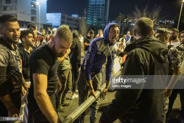 Antigovernment protesters rebuild a roadblock after an hourlong amnesty in which they opened one lane to traffic on the highway entering Beirut on...